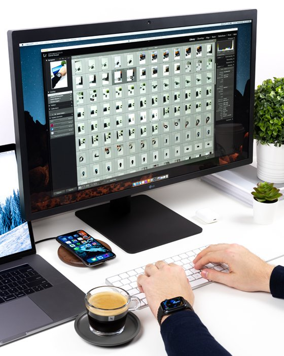 桌上放着一台显示器,旁边放着一杯咖啡、一台笔记本电脑和一部手机