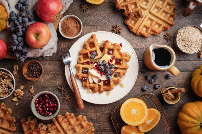 Overhead shot of waffles and fruit on a rustic table