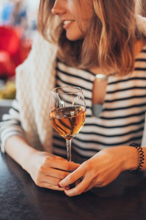 A girl holding a glass of white wine