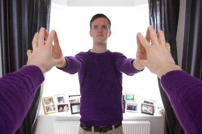 photo of a man reaching for the mirror with both hands