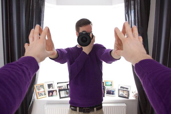 photo of a man taking a photo of himself in the mirror