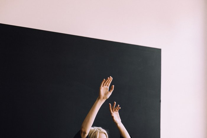 A woman posing with hands in the air