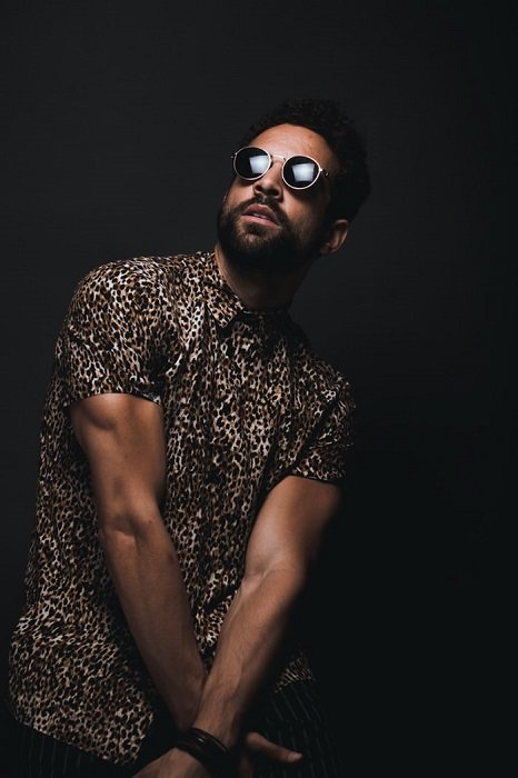 Man posing in front of a black wall in a photography studio