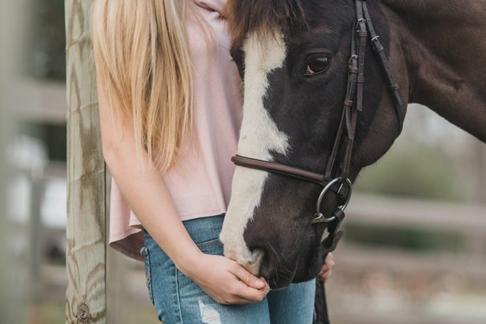 A blonde girl holding a horses bridle