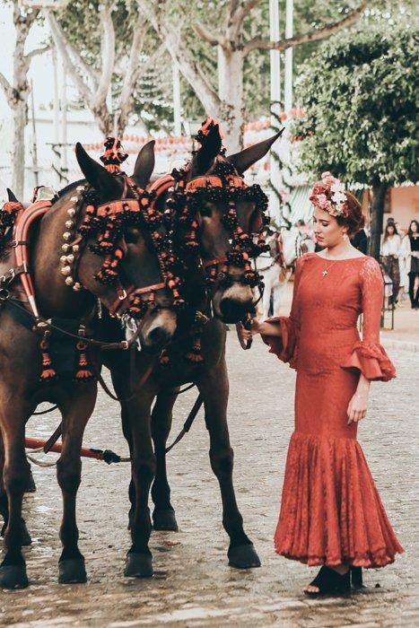 A woman in fancy dress petting two costumed horses