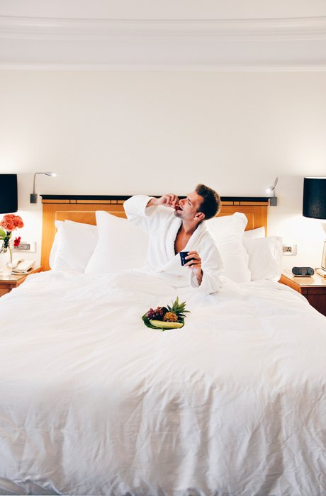A man in a hotel bed eating from a bowl of fresh fruits