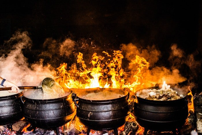 Scene of Indian food being cooked in pots over an open fire