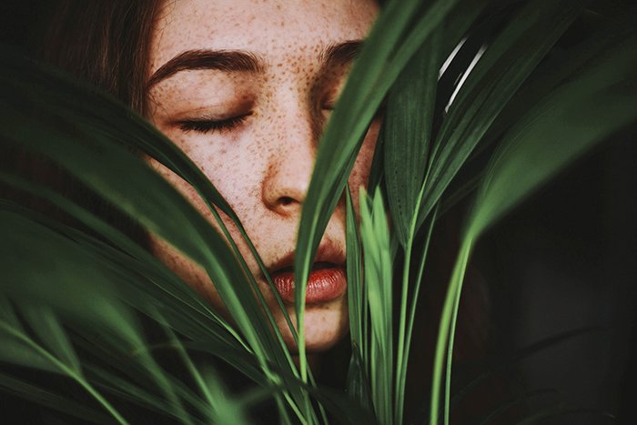 A girl posing indoors covered by plants
