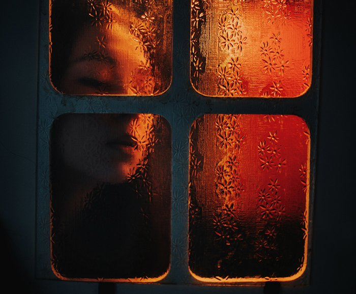 Atmospheric indoor portrait of a girl pushing her face against a window pane