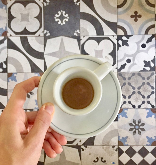A person holding a teacup over patterned tiles