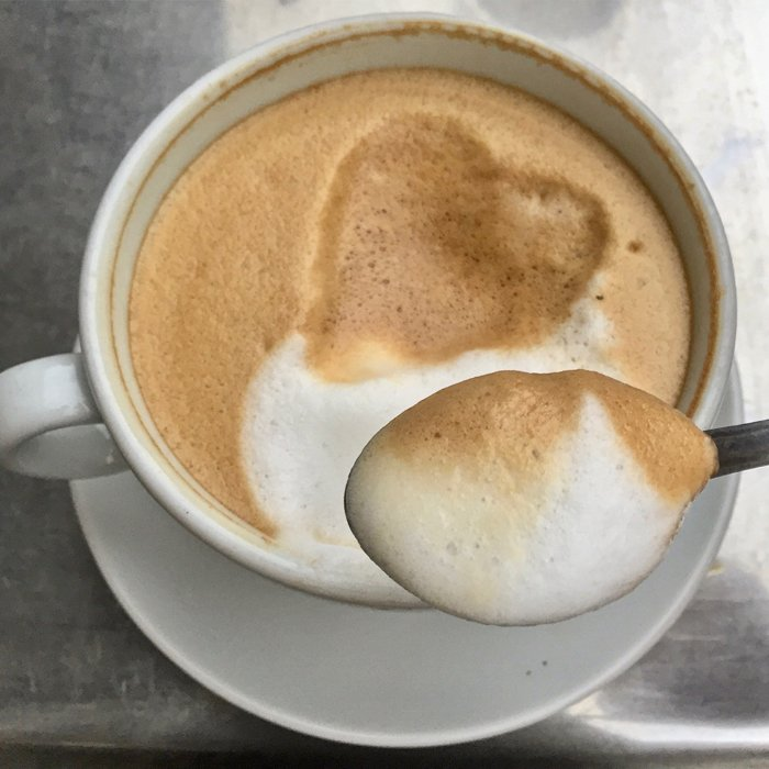 Close up of spooning coffee foam from a cappuccino