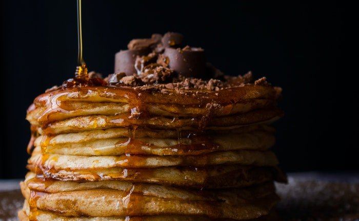 Delicious iphone food photography of syrup being poured on pancakes
