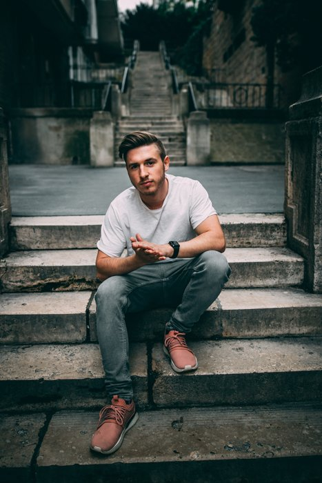 A male model posing casually outdoors on stone steps