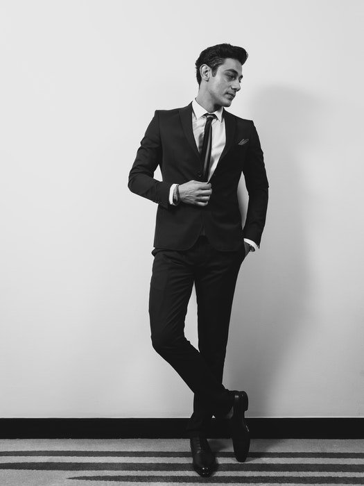 A man in a suit posing casually against a wall