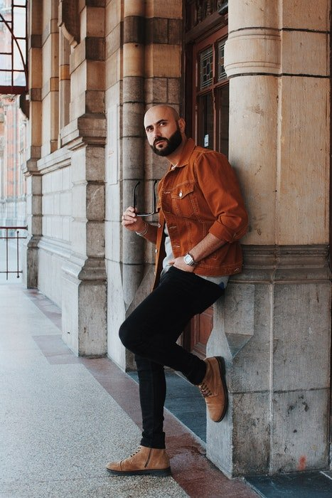 A man in casual dress posing casually against a wall