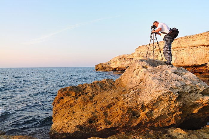 Man standing on rock and taking photo with tripod in blue hour.