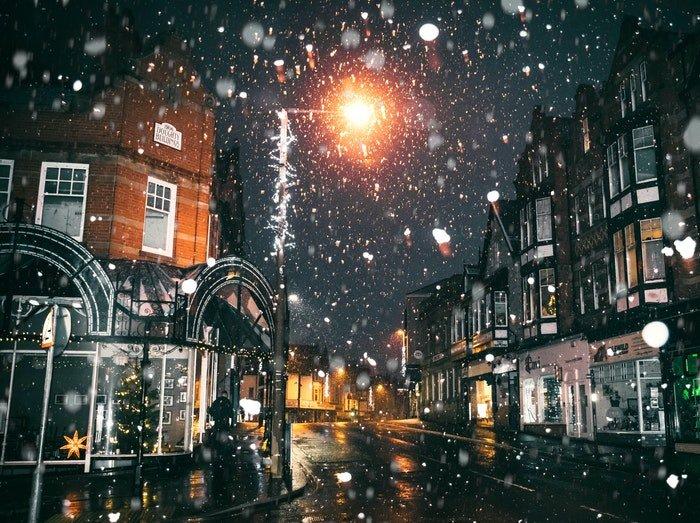 A snowy city street scene at night