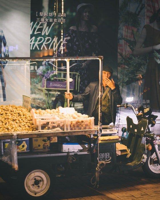 A street vendor smoking at his stall at night