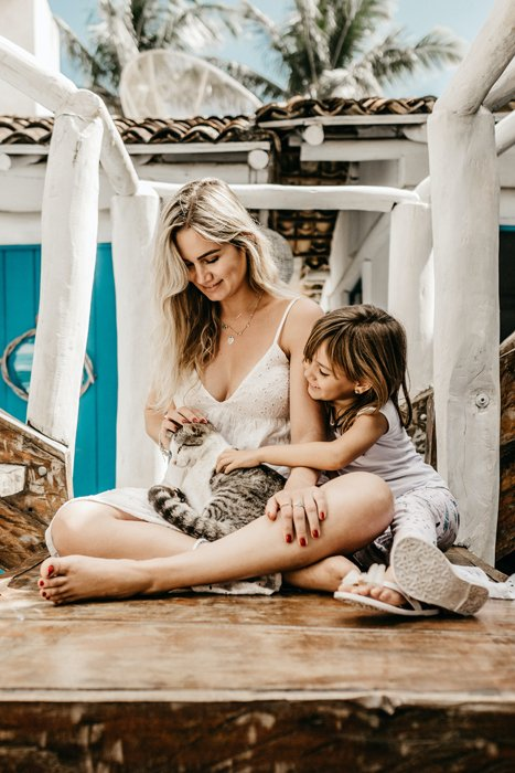 Mother and daughter petting their cat