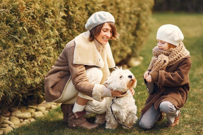 Mother and daughter petting their dog outdoors