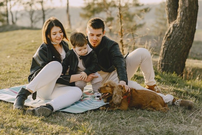 Family portrait having a picnic with their dog