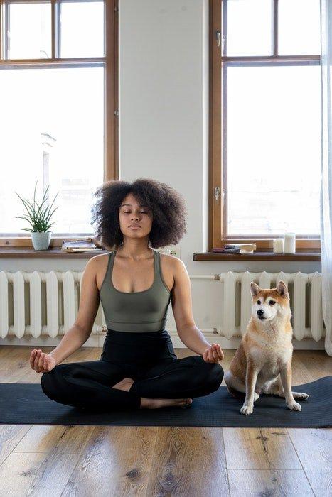 A girl doing yoga beside her cute dog