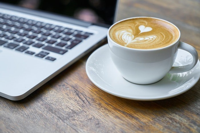 A cup of coffee beside a laptop