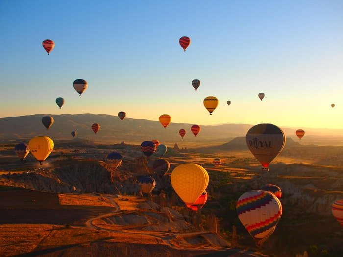 Many hot air balloons floating over a rocky landscape