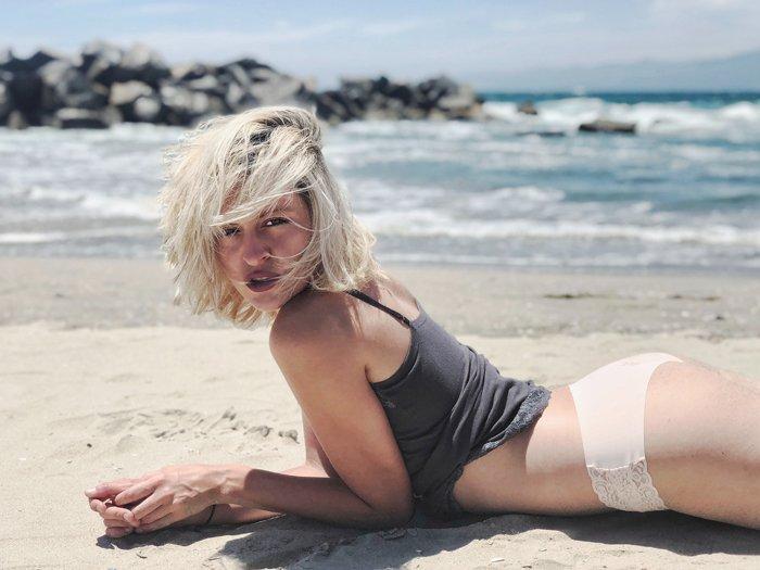 Blonde girl posing lying down on the beach
