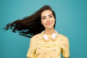 Portrait photo of a woman wearing a ellow tshirt in front of a blue backdrop