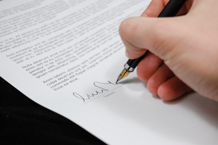 Close up of a person signing a real estate photography contract