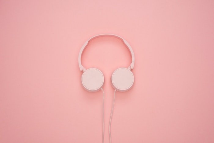 Pink headphones against a pink wall