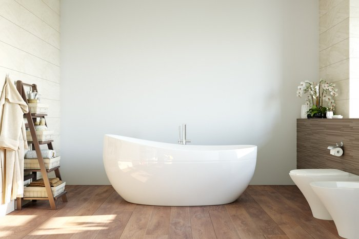 A bathroom with a white bath in the middle. Natural light coming from the window.