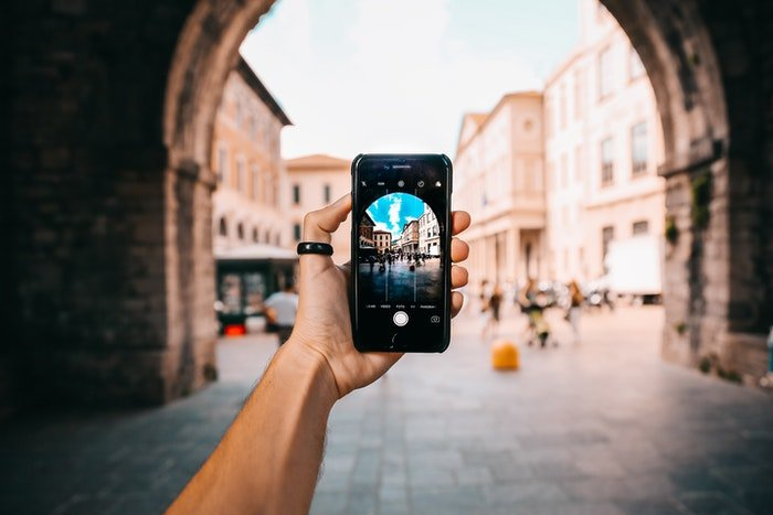 A person taking a smartphone photo of architecture