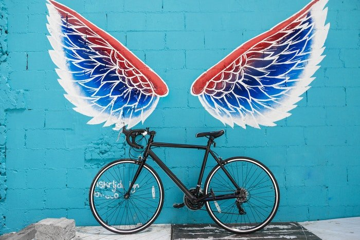 A bike leaning against a graffitied wall