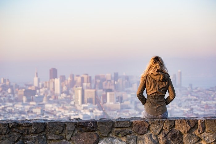 Girl sitting and looking out at urban scene