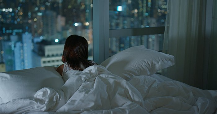Woman looking at the city from window at night.