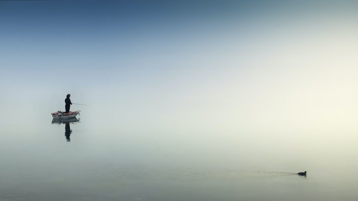 photo of a fisherman on a boat on a lake