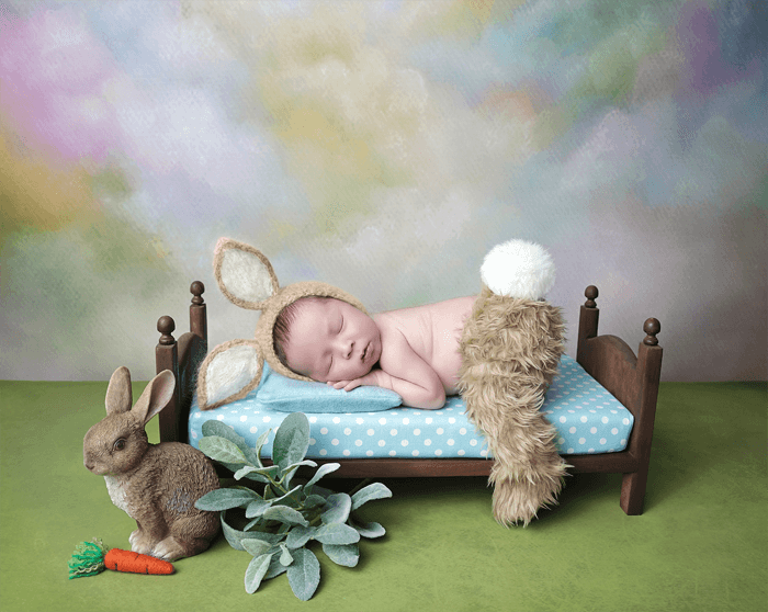 A newborn baby posed in a bunny outfit