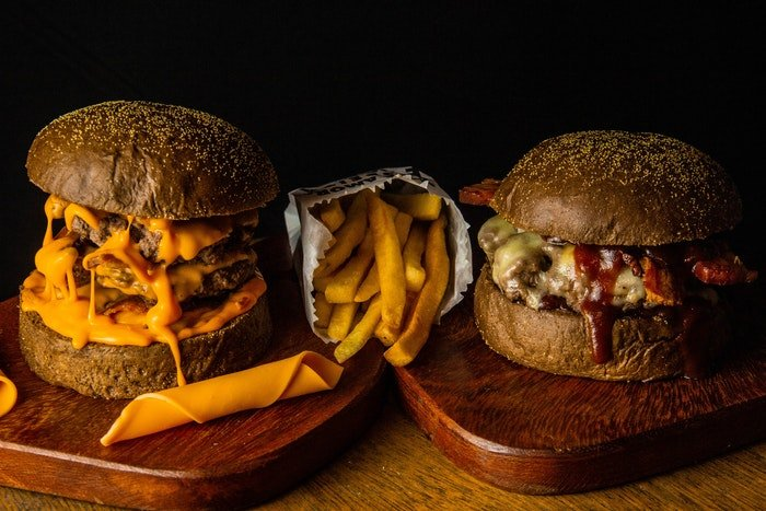 Eye-level photo of two burgers with fries in between