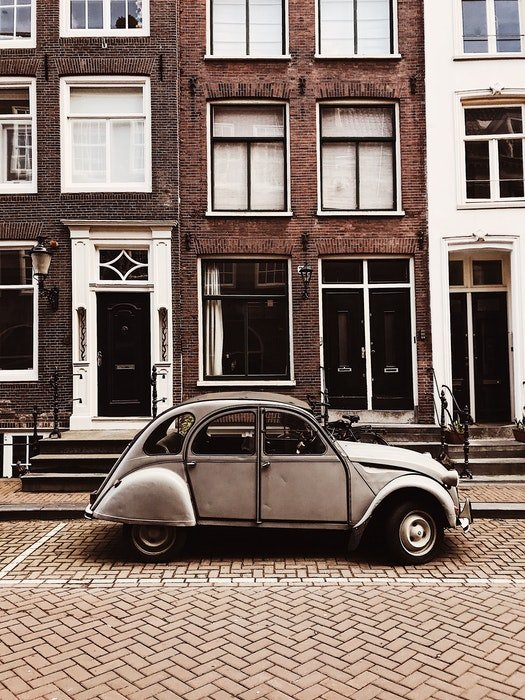 Photo of an old car in front of a brick building