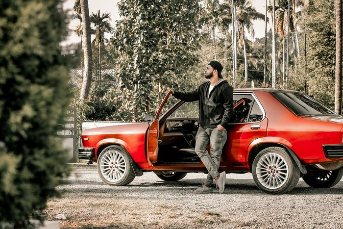 Photo of a man standing next to a red sports car