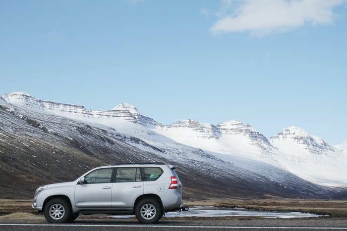 Photo of a silver car with mountains in the background