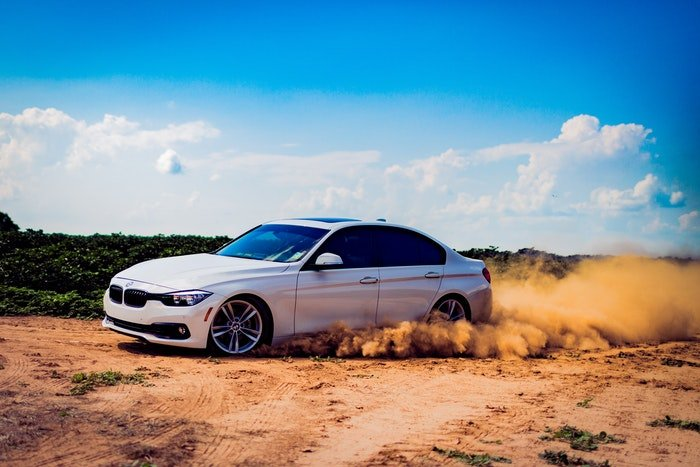 Photo of a driving car on a dirt road
