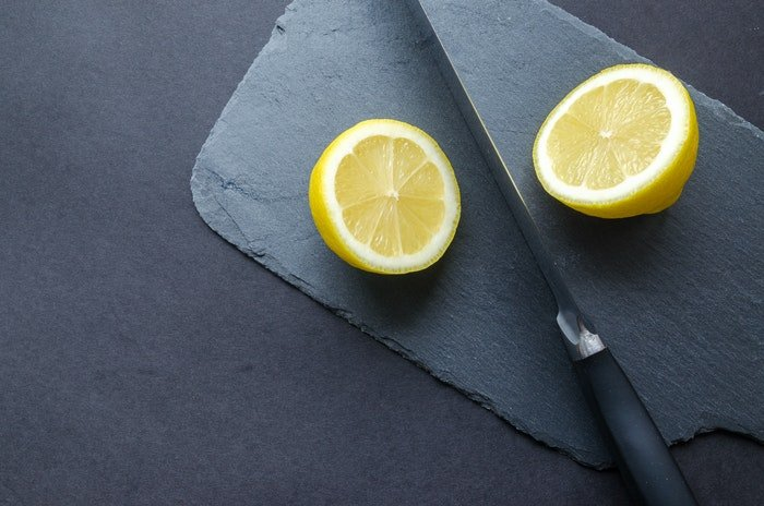 Diy food photography background with a knife and a sliced lemon
