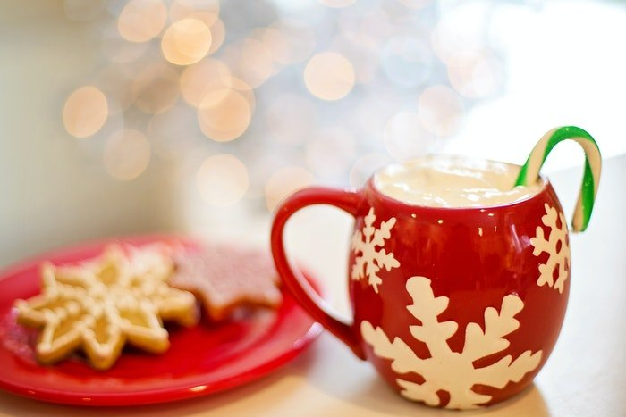A christmas drink beside a plate of cookies