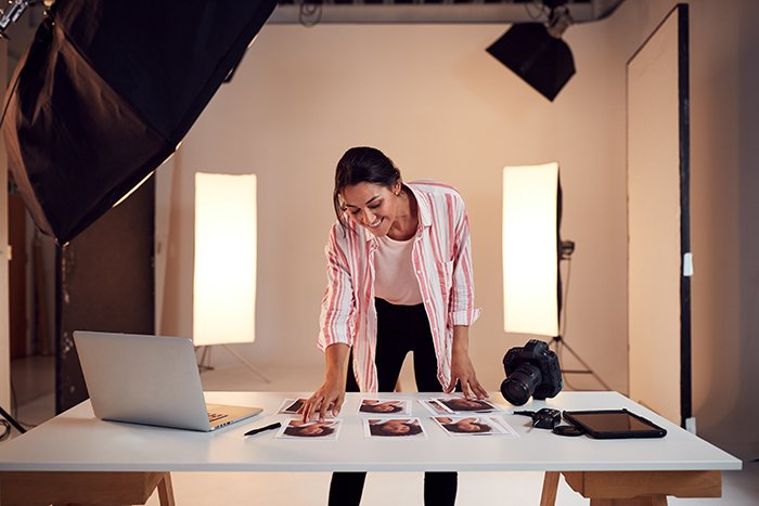 Female photographer is editing images in a photo studio at her home.