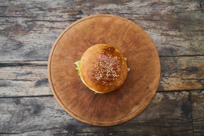 Flat lay food photo of a hamburger on a wooden plate