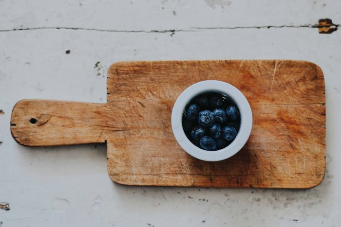 A bowl of blueberries on a wooden chopping board