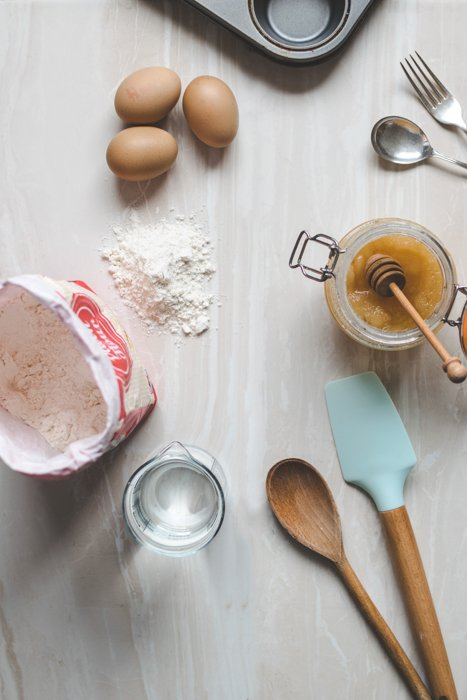 Kitchen utensils, flour and eggs on a marble surface